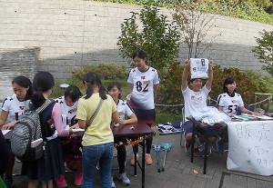 暑さ感じるほどの晴天に恵まれ、「ラクロスフェスティバル」がスタートしました。日吉陸上競技場には子ども達の受付の長い列が。ラクロス部オリジナルのTシャツやタオルの販売も