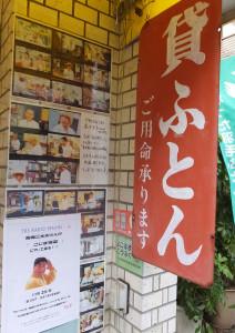 「こじま寝装」の店頭(左下)には生中継を知らせるポスターが貼られている