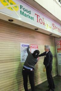 閉店後、シャッターにお知らせを貼り出す東急ストア綱島駅前店のスタッフ(2016年1月8日18時30分ごろ)