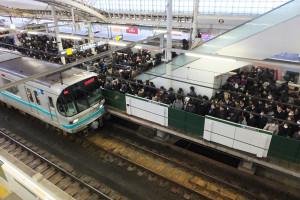 ホームに人があふれる元住吉駅。急行電車が自転車のような速度で通過していた