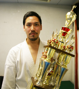 厚木市出身の杉澤一郎さん。日本国際空手協会全日本選手権大会で2009年から3連覇。その腕の確かさ、熱意に満ちた指導で、生徒や保護者たちに支持されている。「優勝」の文字が刻まれたトロフィーと