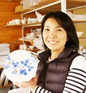 京都生まれ、愛知県育ちという上大迫(かみおおさこ)千絵さん。愛知県立芸術大学で陶磁を学ぶ。作風を感じるワイルド・ストロベリーの絵の作品を手に。「花が好きで、小学校の花ボランティア活動にも力を入れています」と、花や草木の柄で彩る陶芸作品への想いを語ります