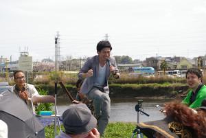 """""""菜の花""""が咲くすぐ横の河川敷の会場に、笑顔と笑いがあふれました(写真中央:乙島山ノブヨシさん)"""