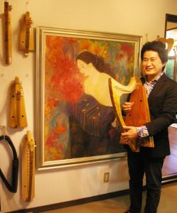 寺本圭佑(けいすけ)さんは京都出身、日吉在住。「お気に入り」だという、妻で日本画家の中井智子さん(リンクはブログ)が絵を描いたという金属弦のアイリッシュ・ハープと、中井さんが描いた日本画の前で撮影