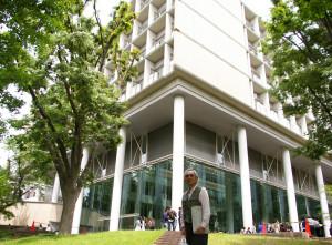 今年2016年から会長に就任した杉山二郎さん。多くの学生が行き交う慶應義塾日吉キャンパスで会場となる「来往舎」前にて。20周年に向けて「新しいことをしていけたら」と意気込みを語ってくれました