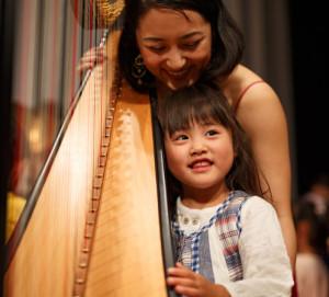 どんな音が出るのかな――終演後に、一部の楽器(ピアノ・ヴァイオリン・ドラム・ベース・ハープなど)の「演奏体験」もあり、様々な楽器に触れ合えるひと時も提供する(プレミアムコンサート事務局提供)
