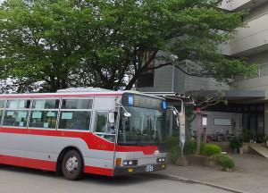 高田町のバス停留所に停車する日吉行のバス。後方に見える建物は「山本記念病院」
