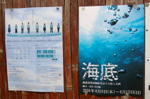 """日吉の街のあちこちにポスターも掲示されている。「日吉の町はとても優しい印象を受けています。とても過ごしやすいところです。一人でいるのも何人でいるのもとても楽しいです。好きなお店は""""祭""""(日吉本町1)という居酒屋さんです」と宮田さん(居酒屋祭前にて撮影)"""
