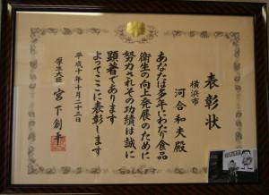 二代目にあたる先代の故・河合和夫さんが厚生省(現在の厚生労働省)に表彰を受けた時の賞状。右下が箕輪町の工場前で遊ぶ幼少時の河合和彦さん