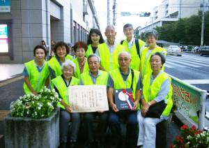 「日吉駅前花壇 花ポケット」ボランティアの皆さん。初代代表の森健(たけし)さんを囲んで。現代表の小出さんは後方左から2番目(2016年9月8日撮影)