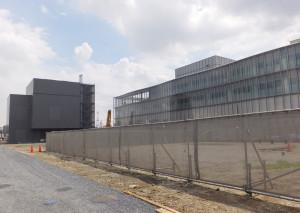 国際学生寮の建設予定地、ガラス張りの建物が米アップルの研究所で左奥は街に電気などを供給する東京ガスのエネルギーセンター(2016年8月24日)