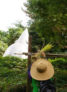 刈り取った稲は10日ほど天日に晒(さら)し、脱穀・精米される予定。左奥は・鳥の広場のシンボルとなっている彫刻・THE BIRD-野生動物「日吉」(1996年・田辺光彰作)