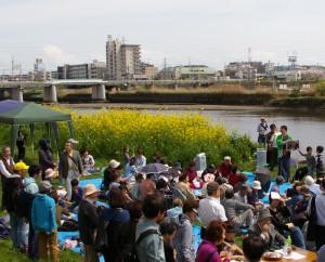 晴天に恵まれた2016年の綱島・鶴見川河川敷での「菜の花まつり」の様子。お笑い芸人「ツナコメ」が今年も登場する(写真は主宰の箸休めサトシさん)