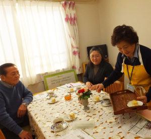 """この日は箕輪町町内会(日吉地区連合町内会)の小島清会長(左)も訪れ、認知症カフェ""""きららカフェ""""に参加。回想法の体験も入居者らと行った。参加費用は「恩返しで」無料とのこと"""
