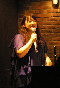 森華燿子(かよこ)さんがピアノと司会進行。「リトルウイングトリオ」の中心として、メンバーや曲目を紹介。ピアノ教室の生徒や家族も多数参加していました