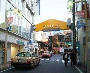 3月中旬まで日吉駅西口のタクシーは、普通部通りではなく「サンロード」をう回して駅前のタクシー乗場へ向かう。右奥の普通部通りアーケード看板の右手が工事が始まった只見ビル