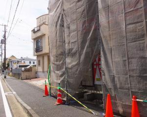 綱島SST側からは綱島街道から反対側、1本裏手に入った通り沿いにある。外壁が布で覆われていることから店頭が見えないが、壁面ガラスに貼り紙で3月16日(金)のオープンを告知している(2018年3月15日12時頃)