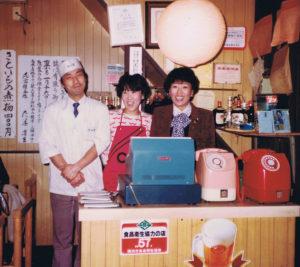 現在、中華名菜龍華(普通部通り)があった場所で、初代女将の河合愛子さん(写真右)は「たつ吉」を創業した。当時は焼き鳥をたしなむ雰囲気のお店だったという(現在地に移転後、改装前の本店にて1983年1月10日撮影、同グループ提供)