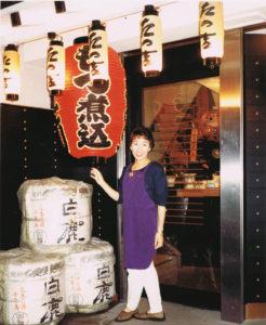"""母・愛子さん(写真)は、仕事で忙しかったため、「夜は妹、弟と4人で過ごしました」と島名さん。愛子さんは、明るく朗らかな人柄で、多くのお客様に""""愛されて""""いたという(現在地の本店が改装オープンした後、1983年10月3日撮影、同グループ提供)"""