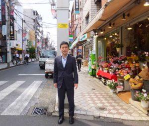 日吉駅西口に面した日吉中央通りの入口付近にて。「多くこれからも受講をお待ちしています」と玉田さん