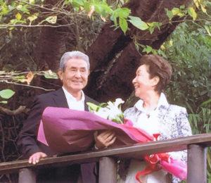 夫で同社会長の芳広さん(左)と、カルチャー日吉20周年の祝賀イベント時に。スタッフから寄せ書きを贈られ、感激したという(栄区の蕎麦店・九つ井(ここのついど)にて、同校提供)