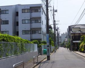 創業当時の「こじま寝装」は、日吉本町3丁目25(左側付近)にあったが、開業から2年もたたない1961(昭和36)年に、この付近で続々建てられたという銀行の寮建設に伴い、現在地に移転。当時の建物を引き車でひっぱってきたという。道路奥は日吉台中学校