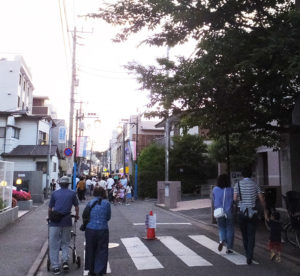 桜大門の横を多くの人々が通り抜け、今年も夜店に来訪する。「孫と夜店に参加するために、電車に乗ってきました」と言われたのがとても嬉しかったという(2017年6月3日撮影)