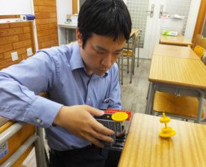 """ひよし塾で開講中の「ロボット教室」の教材を使用したこままわし。「あらゆる角度から、楽しく学べる機会、""""粘り強く""""考えることができる人材を育てたい」とその夢は大きく広がる"""