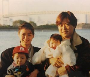 新聞販売店に入店した頃の乙幡さん(右)。妻のいずみさん、授かった2人の子と東京・お台場で(1996年頃、乙幡幸雄さん提供)