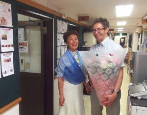 日吉独自のカルチャー・センターとして親しまれる「カルチャー日吉」創業者・代表の高松汀子さん、「英語でピアノ」や、「英語でポピュラーソング」のコースも担当するネイティブ講師のコーリー・ストロハンさん。パパになったコーリーさんを同校で祝福(カルチャー日吉提供)