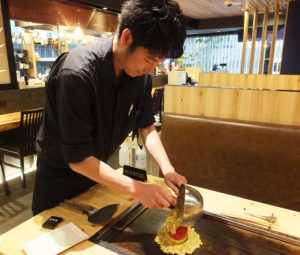30年来の伝承の味「トマトまるごとチーズ玉」を焼いてくれた店長マネージャーの斉藤優士(ゆうじ)さん。「焼き方をマスターするまで、時間がかかりました」とのこと