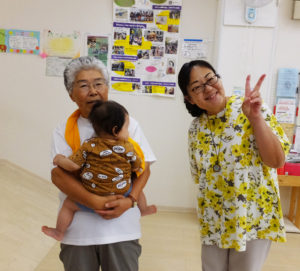 """人気の小さな「すべり台」前で。橋本さんと神島さん(右)。「綺麗になった娘さんが、""""お世話になりました""""と突然戻ってきてくれることがあって。びっくりし、心から嬉しく思います」と、橋本さんらは""""誰もが顔見知り""""、そして""""戻れる""""場所としてのこの街をより育みたいという"""