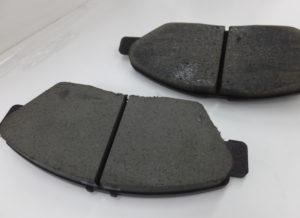 削れて薄くなったブレーキパッド(奥)と新品。新品は約1センチメートル(cm)ほどの厚み。「ブレーキ診断保証」で、使用限度(経過月・もしくは走行距離)を保証するなど、無駄な部品交換は行わない