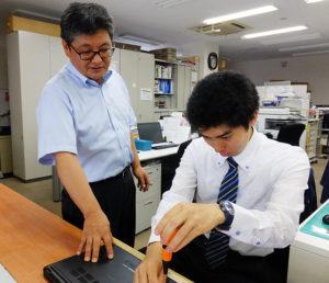 「パソコン救急センター」事業をリードする井上健司さん(左)はこの道30年来のベテラン。「地域により溶け込んだ事業を行いたい」と若手社員・スタッフの採用や育成指導にも想いを寄せる