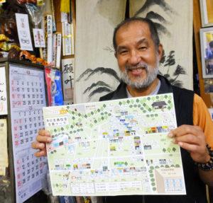 「生まれ変わったイラストマップをご利用ください」と商店街をPRする会長の小嶋純一さん