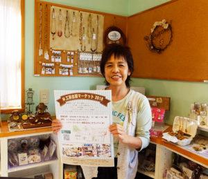 綱島駅から徒歩約8~9分、イトーヨーカドーや綱島小学校から徒歩約5分の場所にある「M工房」オーナーの小泉美菜さん。届いたばかりの「出張マーケット」のポスターを手に