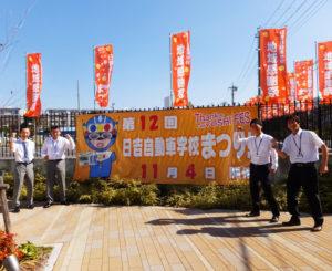 第12回日吉自動車学校まつりの開催迫る!昨年は過去最高の人出で盛り上がった。写真は左から、同校の宮越健輔さん、加藤大さん、実行委員長の井手健嗣さん、山本雄介さん。同校オリジナル・キャラクターの信号マンと