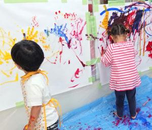 芸術アートに造詣が深い三井律子(みついりつこ)さんが講師を担当する「キッズガーデン~プレ幼稚園」では、大きなキャンバスに伸び伸びと絵を描くシーンも(カルチャー日吉提供)