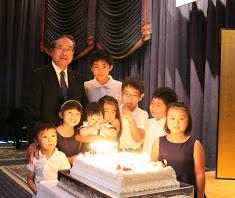 """創業40年パーティーで孫たちに囲まれる青木廣志さん。新しい未来へと進む若手""""人財""""とともに、これからも税理士としての歩みを続けていく(同税理士法人提供)"""