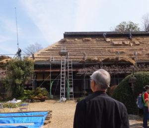 飯田助知さん(手前)が見守る中、「港北ふるさとテレビ局」(伊藤幸晴代表)も葺き替えの様子を撮影取材していた