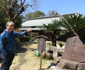 池谷家16代当主の道義さん。池谷家住宅にある日月桃の碑と。住宅前の庭には花桃を植えている(3月18日)