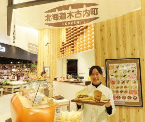 木古内出身の店長・大野さん。ゴールデンウィーク中に割引価格で販売する予定の「ステーキコッペ」と「塩パン5個セット」を手に