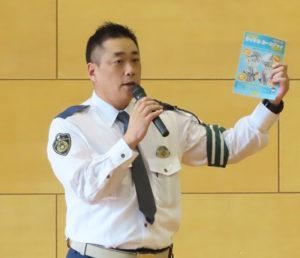 港北署交通課の堀井さんが区内の事故を報告。授業を受けた生徒に配布した「みんなのサイクル ルールブックよこはま」を手にとり、高額賠償の事例についても注意喚起した