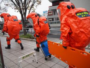 特別高度救助部隊(綱島)が、負傷者の救出と撒かれた液体の除染処理へ。「進入統制ライン」より向こう側へは一般の人は入れない