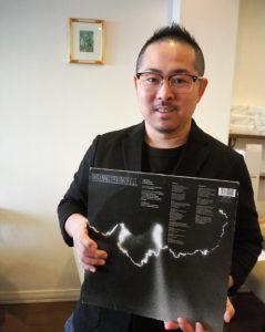 池田さんが浜銀通りで経営する店の名前の由来となった、イギリスのロックバンド・オアシスのレコード「ワンダーウォール(Wonderwall)」を手に