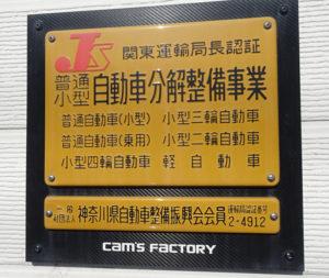 「神奈川県自動車整備 港北支部」に加盟する事業者が掲げる『黄色い認証マーク』。自動車整備士資格や作業スペース、機械工具類といった国が定める基準をクリアした「認証工場」として、国土交通省関東運輸局から認証を受けている