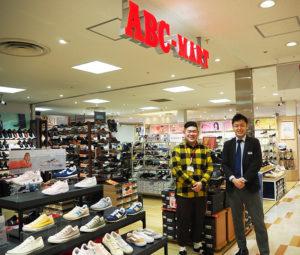 この3月で2周年を迎えたABCマート(ABC-MART)日吉東急アベニュー店の宮本昌英ストアマネージャー(左)。日吉東急アベニューの元林正輝マネジャーと