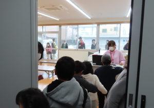 キッズクラブ専用の部屋で、まずはその日の利用受付。窓越しに保護者らが子どもたちを見守っていた