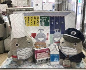 日吉駅の改札口横に置かれた、2体の「着せ替えのるるん」。現在のテーマはマスク着用奨励・飲食店支援バージョン。その装いを変えながら、駅を行き交う人々を窓越しに眺めている(5月25日、東急日吉駅提供)