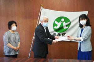 港北区役所で、河野社長に「お礼状」を送る栗田区長。最左は同社総務担当の綱川さん